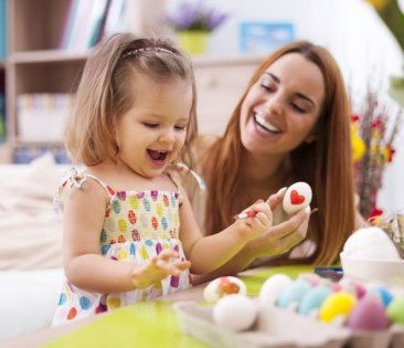 happy kid painting something on an egg with a middle aged woman