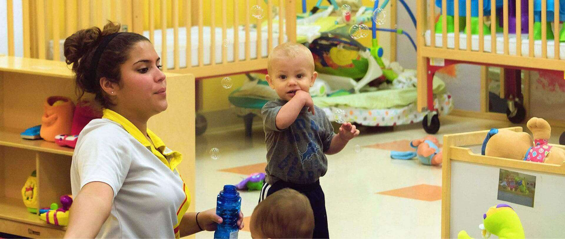 a teacher playing bubbles with kids